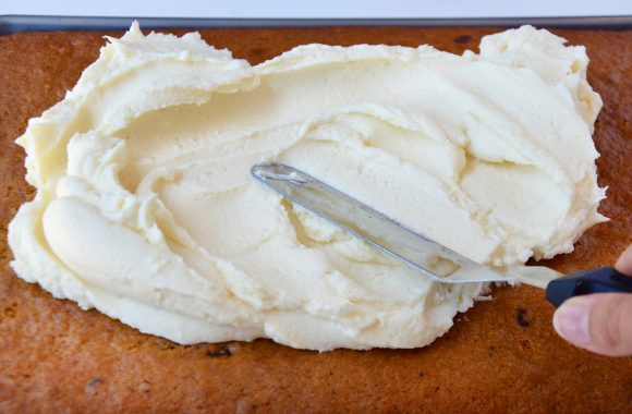 Spreading cream cheese frosting on pumpkin bars