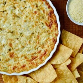 Top down view of Hot and Creamy Artichoke Dip next to tortilla chips