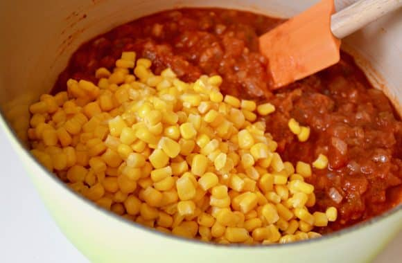 A stock pot containing Salsa Corn Chowder with a pile of yellow corn