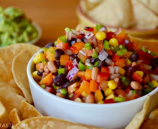 A white bowl with Texas Caviar and a white plate with tortilla chips