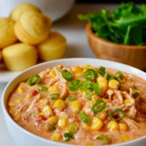 A white bowl containing Salsa Corn Chowder with a plate of corn muffins behind it