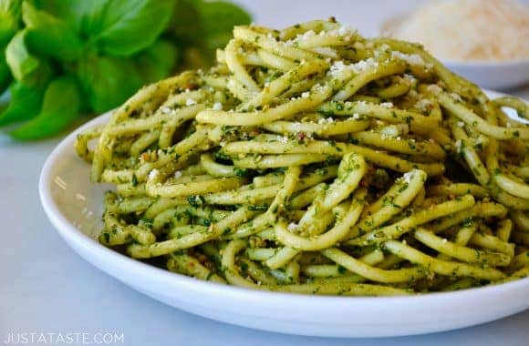 Basil pesto bucatini pasta on a white plate