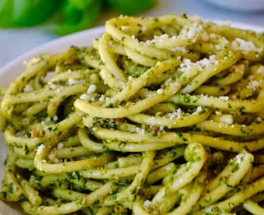 Basil pesto pasta on a white plate with basil and cheese