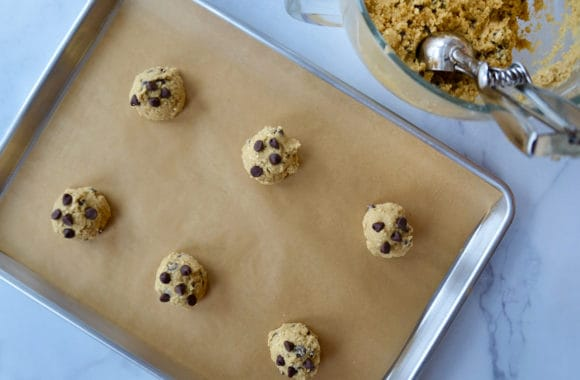 Scooped balls of cookie dough on parchment paper-lined baking sheet next to bowl containing cookie dough and scoop