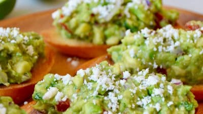 Guacamole bruschetta toasts on a wooden plate