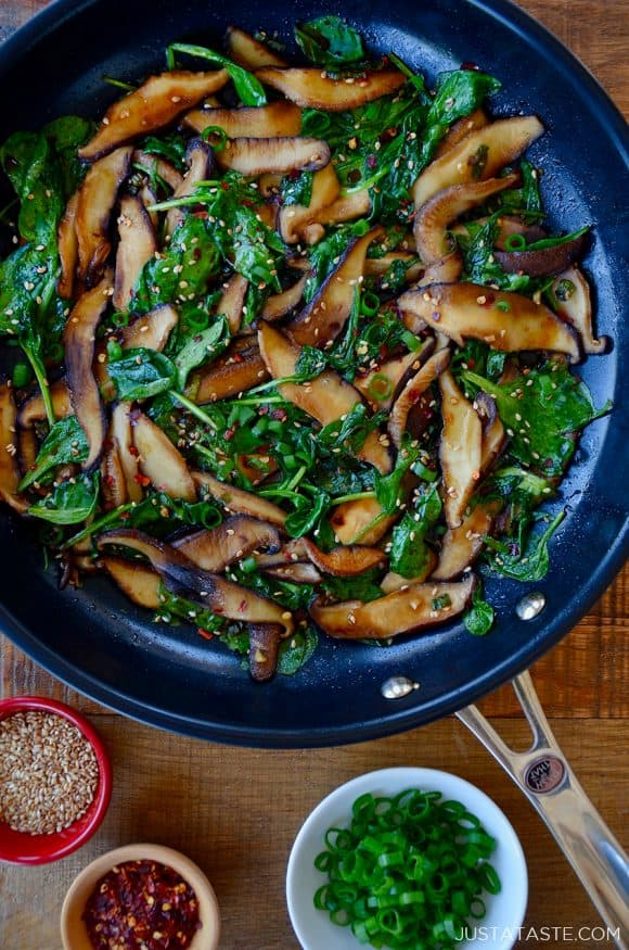 Skillet with sauteed mushrooms and spinach in a spicy garlic sauce