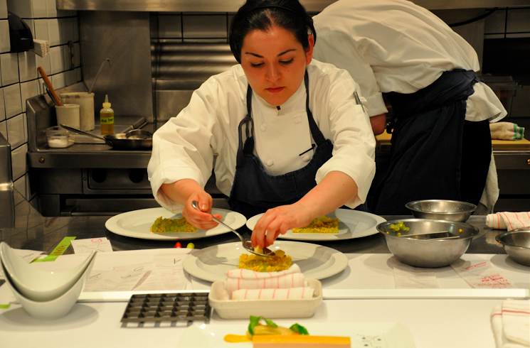 A chef at the plating section arranges a bed of roasted corn for the next course to be delivered.