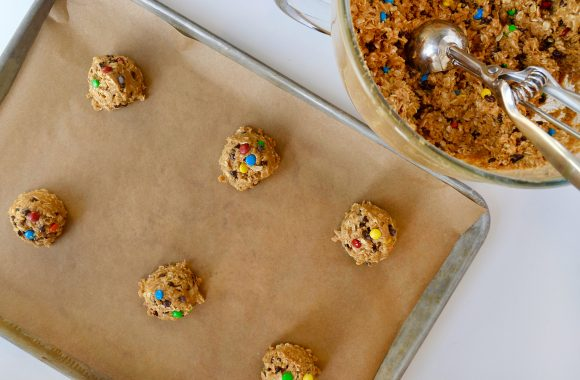 Unbaked cookies on baking sheet with cookie scoop