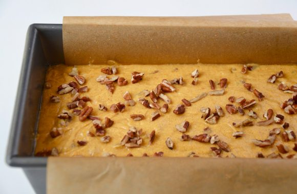 The Best Pumpkin Bread batter in a parchment paper-lined bread pan
