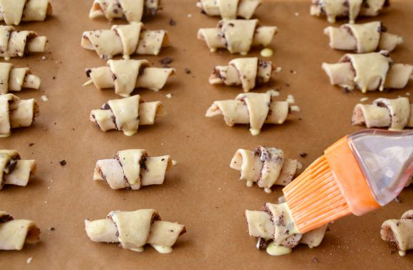 Applying egg wash to chocolate rugelach with brush
