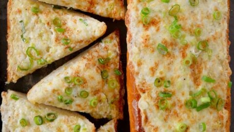 A baking sheet containing a loaf of garlic bread cut into triangles