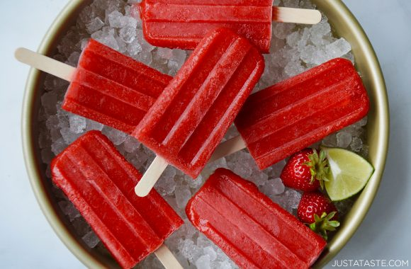 Easy strawberry margarita popsicles over ice next to lime wedge and fresh strawberries