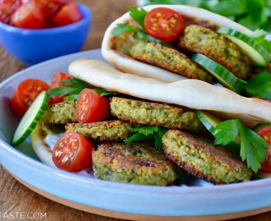 Easy Homemade Falafel tucked inside pita bread with Tahini Sauce, cucumbers, tomatoes and parsley. Small blue blue with cherry tomatoes in background.