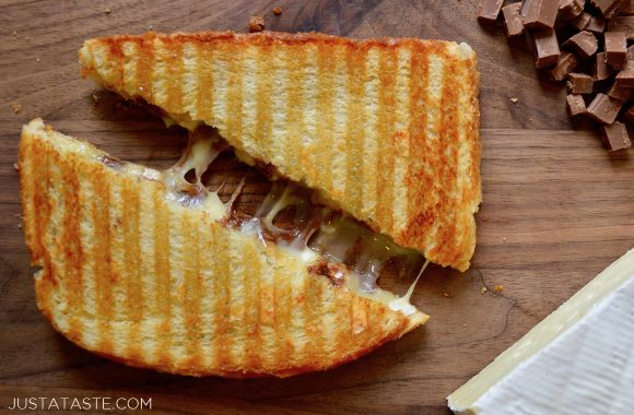 A chocolate and brie panini sandwich cut in half on a wood cutting board