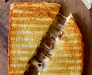 A Chocolate and Brie Panini sandwich on a wood cutting boar