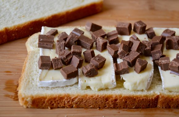 A slice of white bread topped with brie cheese and chopped chocolate on a cutting board