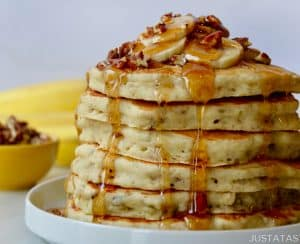 Tall stack of Banana Nut Pancakes topped with sliced fresh bananas, pecans and maple syrup on white plate with small bowl filled with pecans and bananas in background