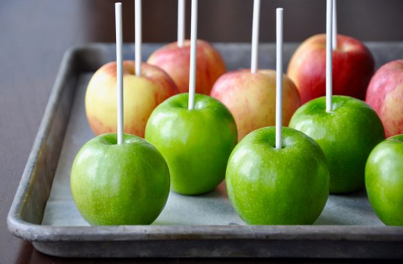 Green and red apples with white sticks for candy apples