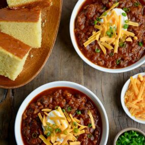 Two white bowls containing pumpkin turkey chili with a plate of cornbread