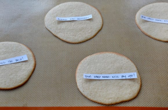 Handwritten fortunes on top of baked cookies
