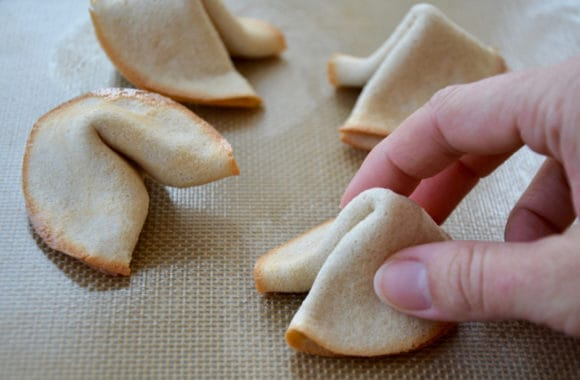 Hand shaping fortune cookies