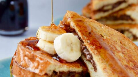 Banana and Nutella Stuffed French Toast topped with banana slices and drizzled with maple syrup