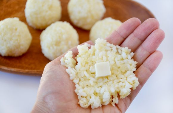 Hand with rice and mozzarella cheese to form arancini ball