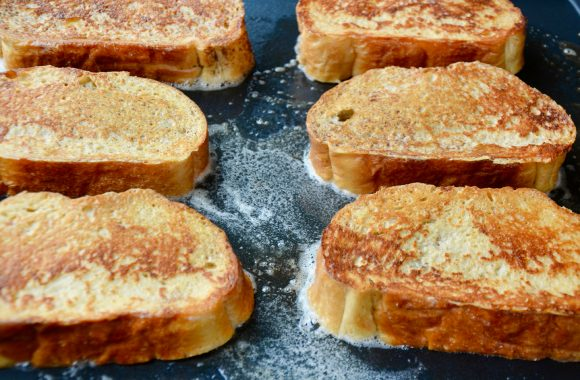 Frying stuffed French toast in large skillet containing butter