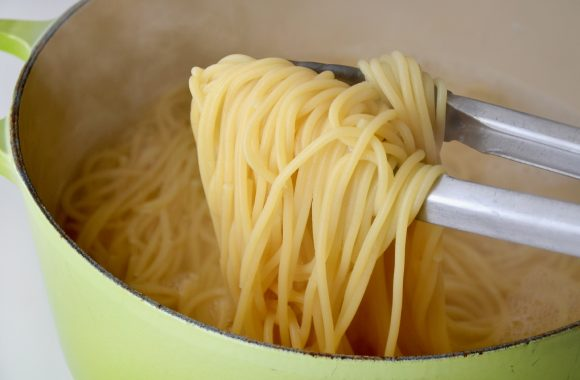 Green pot with cooked spaghetti and tongs