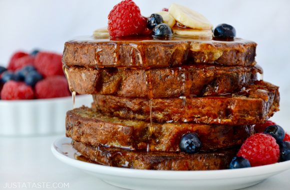 Stack of Banana Bread French Toast topped with fresh fruit and pure maple syrup