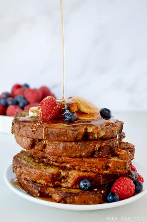 Stack of Banana Bread French Toast with maple syrup drizzle and fresh fruit