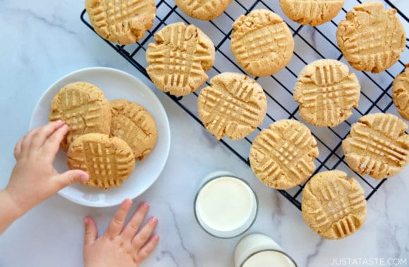 Homemade peanut butter cookies atop a wire cooling rack next to two glasses filled with milk and a child's hands reaching for plate of cookies