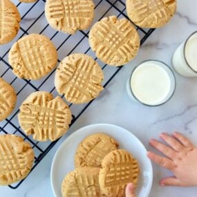 Child's hand reaching for Soft and Chewy Peanut Butter Cookies on white plate next to glasses of milk and wire cooling rack with cookies