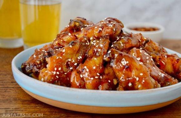 Crispy baked orange chicken wings just a taste pin it crispy baked orange chicken wings on pale blue plate garnished with sesame seeds two glasses forumfinder Gallery