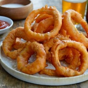 A plate of onion rings with Ranch dressing, ketchup and beer in the background