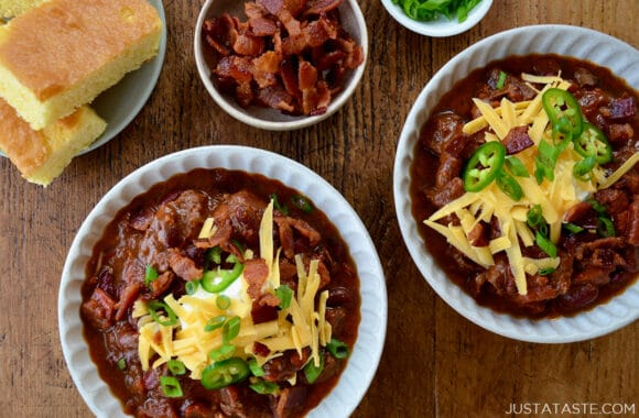 Top-down view of bowls of homemade Chili con Carne topped with, sour cream, shredded cheddar cheese and jalapeños next to a small bowl containing pieces of bacon and a plate with cornbread