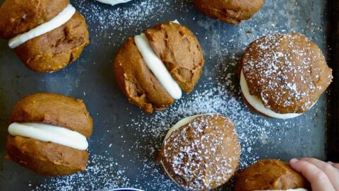 A baking sheet with whoopie pies and little kids' hands grabbing them