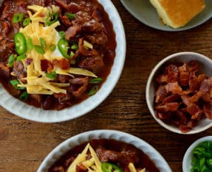 Top-down view of bowls of Chili con Carne topped with, sour cream, shredded cheese and jalapeños next to a small bowl containing pieces of bacon and a plate with cornbread