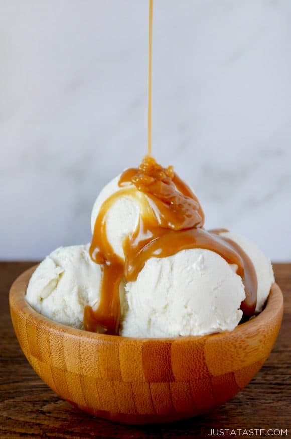 Easy Homemade Butterscotch Sauce poured over vanilla ice cream in wooden bowl