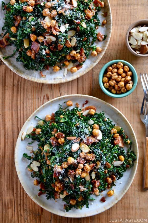 Two white plates piled high with kale salad with a small bowl of crispy chickpeas next to it