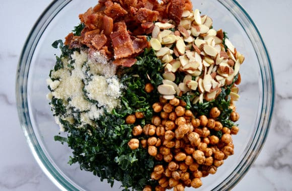 A glass bowl containing shredded kale, chickpeas, bacon, cheese and almonds