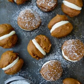 A baking sheet with pumpkin whoopie pies and a sieve with confectioners' sugar