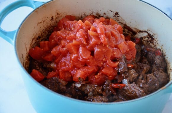 Large blue stockpot containing diced tomatoes over seared meat