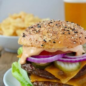 A cheeseburger on a white plate with chips and a beer in the background
