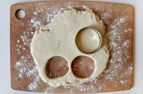 Shortcake biscuit dough on floured cutting board with circular shapes cut out.