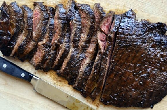 Sliced flank steak on cutting board with sharp knife