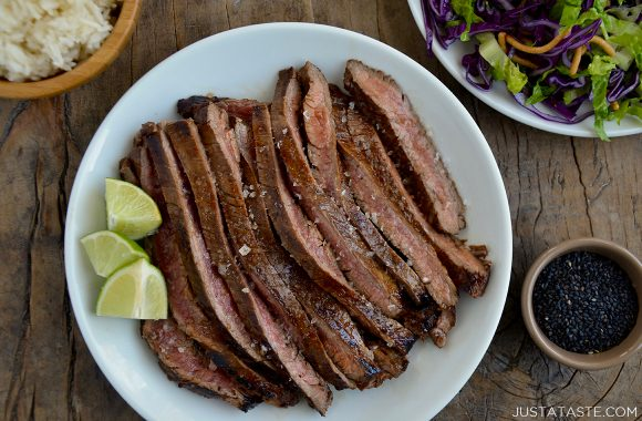 Sliced Asian flank steak on white servings plate with lime wedges