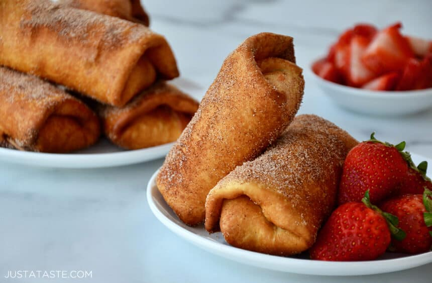 Strawberry Cheesecake Chimichangas on a white plate next to fresh strawberries
