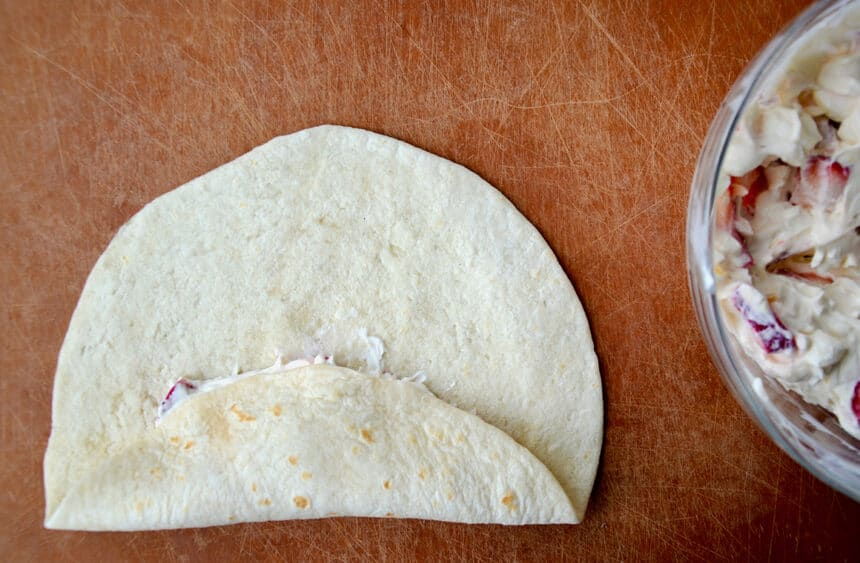 Flour tortilla folded over filling next to a bowl containing cream cheese and fresh fruit