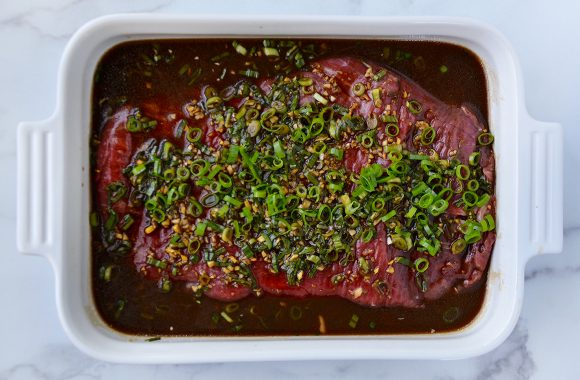 Flank steak in Asian marinade topped with minced garlic and ginger, and thinly sliced scallions